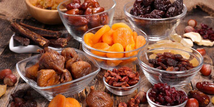 Verschiedene getrocknete Früchte in Glasschüsseln auf einem Holztisch