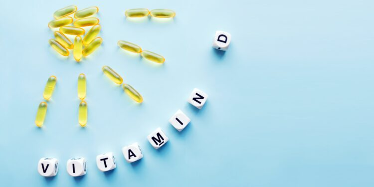 Gelbe Kapseln formen eine Sonne und Sonnenstrahlen; darunter der Schritzug Vitamin D.