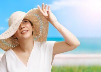 Frau mit Hut schaut in die Sonne.