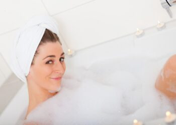 Eine Frau in der sitzt in der Badewanne mit viel Schaum