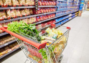 Ein mit Lebensmitteln bepackter Einkaufswagen steht in einem Supermarkt.