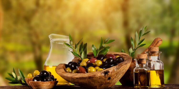 Oliven und Olivenöl auf einem Holztisch.