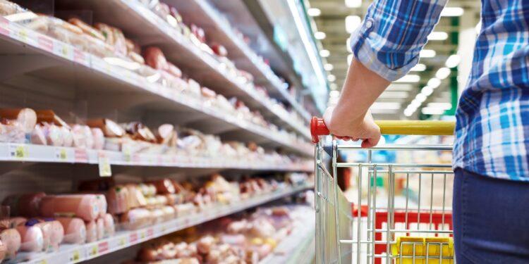 Eine Person schiebt einen Einkaufswagen an einem Wurstregal im Supermarkt entlang.
