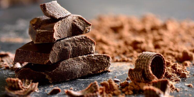 Schokoladenstücke, Schokopulver und Schokoraspeln liegen auf einer dunklen Oberfläche.