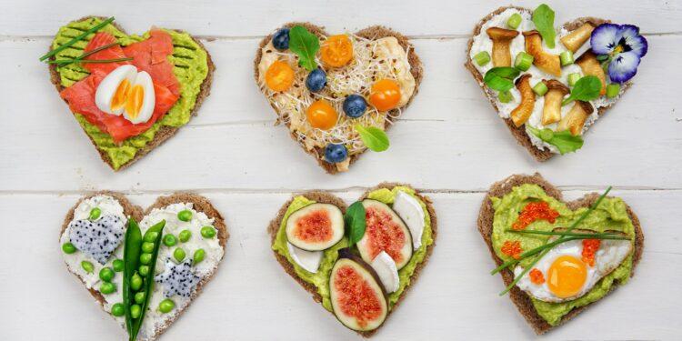 Brotscheiben in Herzform, die mit gesunden Lebensmitteln belegt sind.