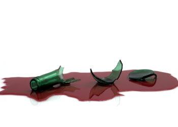 Scherben einer Weinflasche liegen in einer Lache aus roter Flüssigkeit.