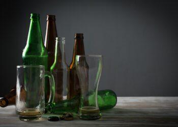 Auf einem Tisch stehen leere Bierflaschen und Gläser.