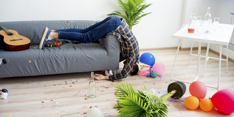 Ein Mann schläft halb aus dem Sofa hängend in einem unordentlichen Zimmer.