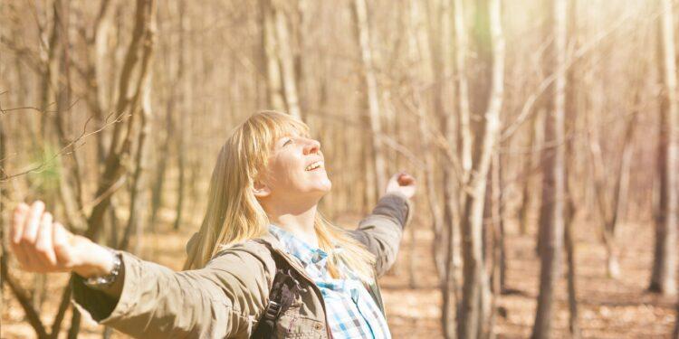 Frau genießt Sonnenstrahlen bei einer Wanderung im herbstlichen Wald