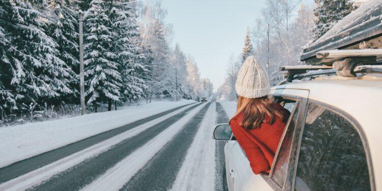 Eine Frau steckt ihren Kopf aus dem Fenster eines Autos.