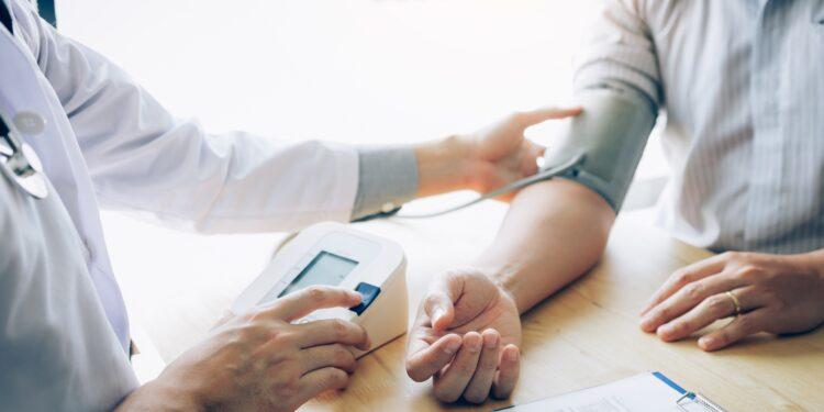 Ein Arzt misst den Blutdruck eines Patienten.