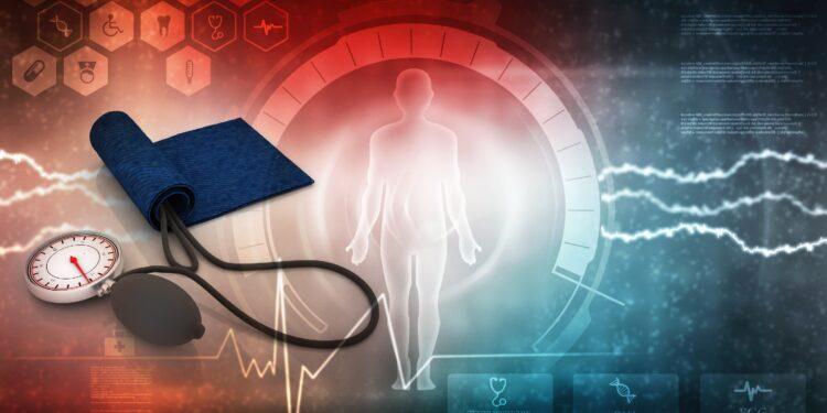 Blutdruckmessgerät vor der Grafik eines menschlichen Körper und einer EKG Kurve.