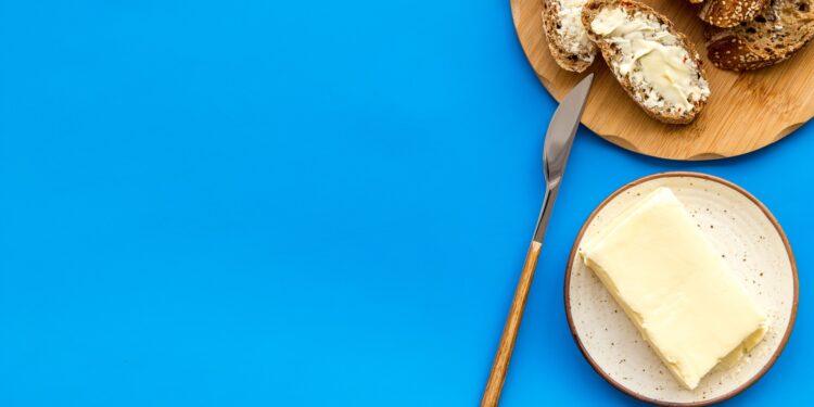 Messer, Butter und ein Brot mit Butter auf einem Holztablet vor blauem Hintergrund.