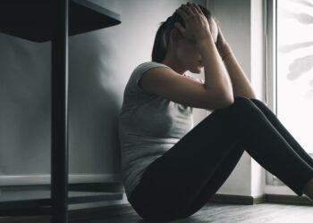 Depressive Frau sitzt auf dem Bodem im dunklen Zimmer, bedroht durch Coronaviren.