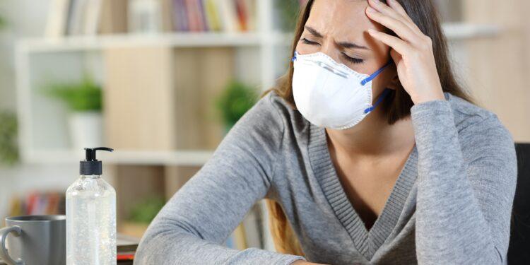 Frau mit Mund-Nasen-Bedeckung sitzt mit schmerzverzerrtem Gesicht am Tisch
