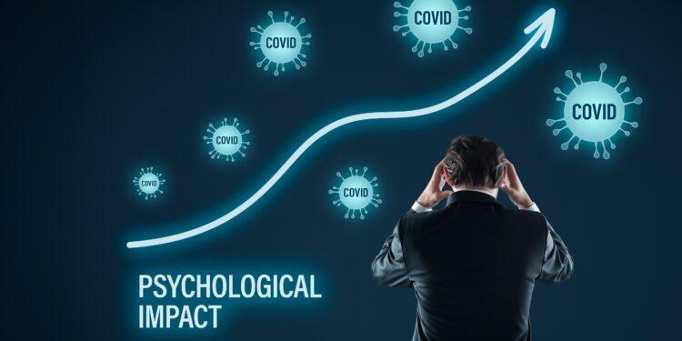 """Gestresster Mann im Anzug der sich an den Kopf fast umringt von simulierten Coronaviren und einer steigenden Linie mit der Unterschrift """"Psychological Impact""""."""