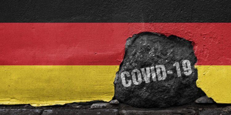 """Eine Deutschlandfahne mit einem Loch in dem """"COVID-19"""" steht."""
