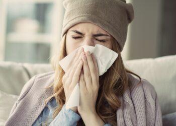Erkältete Frau putzt sich die Nase.