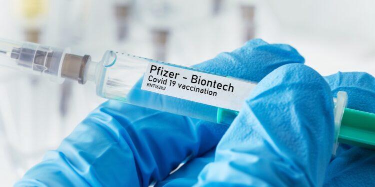 Behandschuhte Hand mit Spritze mit Impfstoff von Pfizer - Biontech