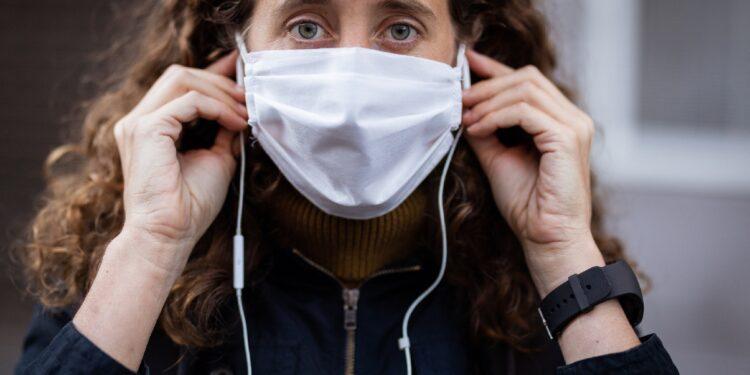 Frau mit Mund-Nasen-Bedeckung und Ohrstöpsel-Kopfhörern