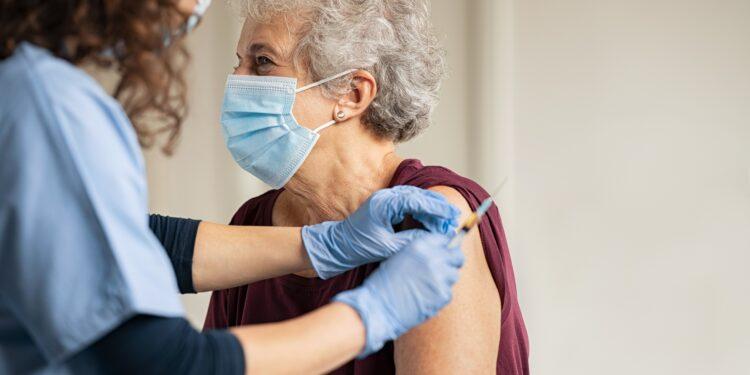 Ärztin impft eine ältere Frau