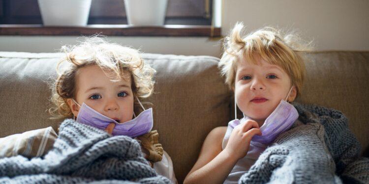Zwei kleine kranke Kinder mit Gesichtsmaske zu Hause im Bett liegend