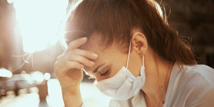 Gestresste Frau mit Gesichtsmaske berührt die Stirn.