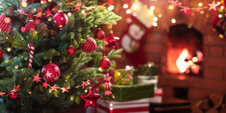 Geschmückter Weihnachtsbaum und Geschenke vor einem Kaminfeuer