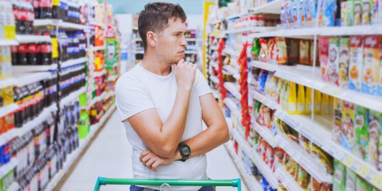 Ein Mann mit nachdenkender Körperhaltung steht vor einem Getränkeregal im Supermarkt.