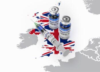 Auf einer Karte von Großbritannien liegt eine Spritze und zwei Dosen eines COVID-19-Impfstoffes.