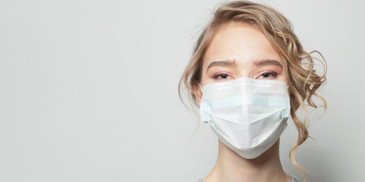 Junge Frau mit Mundschutz