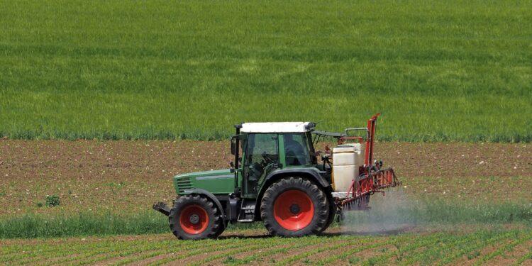 Traktor beim Versprühen von Pflanzenschutzmitteln auf einem Acker