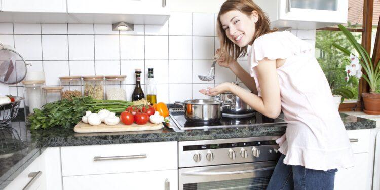 Eine Frau kocht mit gesunden Lebensmitteln.