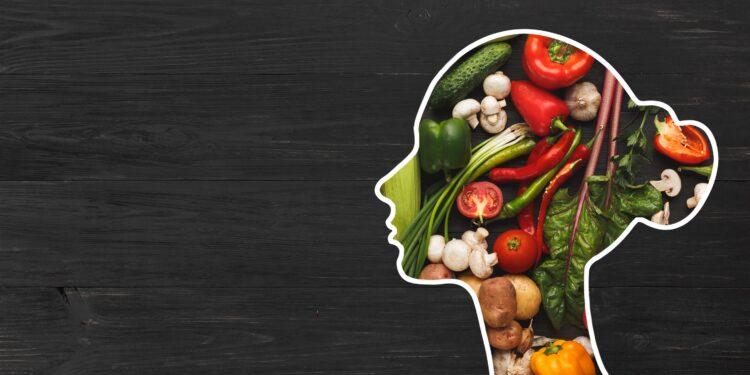 Silhouette eines Frauen Kopfes gefüllt mit gesundem Obst und Gemüse.
