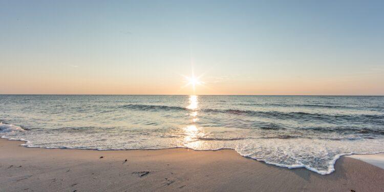 Strand am Meer mit Sonne am Horizont