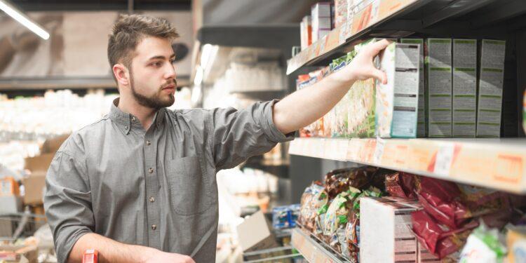 Ein Mann nimmt eine Packung Müsli aus einem Regal im Supermarkt.