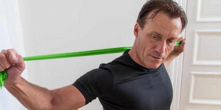 Ein Senior trainiert die Muskeln mit einem Fitnessband.