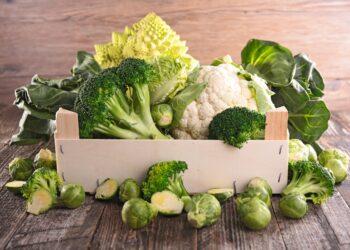 Verschiedenes Gemüse wie Brokkoli, Rosen- und Blumenkohl in einer Holzkiste und auf einem Holztisch