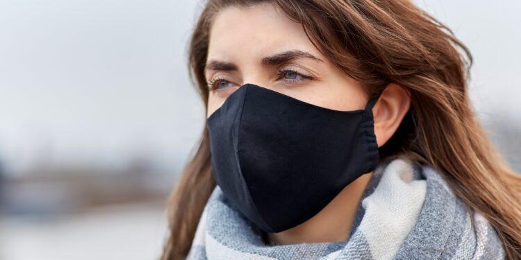Eine Frau im Freien mit einer schwarzen Mund-Nasen-Bedeckung