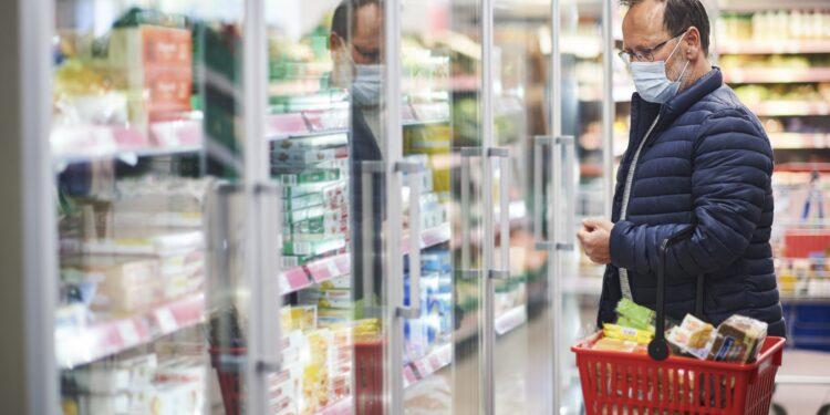 Mann mit Mund-Nasen-Bedeckung mit Einkaufskorb beim Einkaufen im Supermarkt