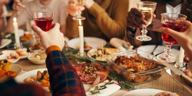 Feunde stoßen mit einem Glas Wein beim Weihnachtsessen an.
