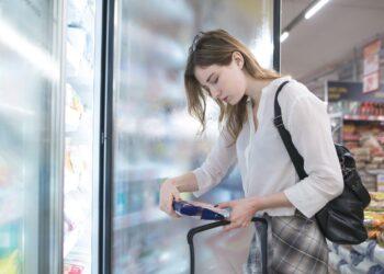 Eine Frau nimmt ein Produkt aus einem Tiefkühlregal im Supermarkt.