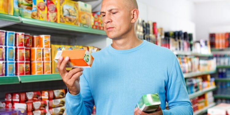 Ein Mann im Supermarkt ließt sich das Etikett auf einer Teeverpackung durch.