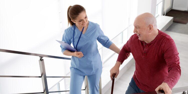 Eine Krankenschwester hilft einem älteren Mann beim Treppensteigen.