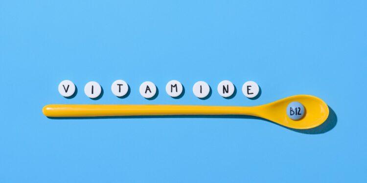 Ein gelber Plastikkochlöffel auf blauem Hintergrund mit der Aufschrift Vitamine B12