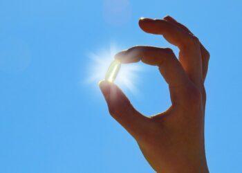 Eine Hand hält eine Pille vor die Sonne.