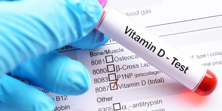 """Eine Hand hält ein rotes Röhrchen mit der Aufschrift """"Vitamin D Test""""."""