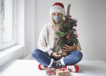 Eine Frau mit Alltagsmaske sitzt vor einem Fenster und wartet auf Weihnachten.