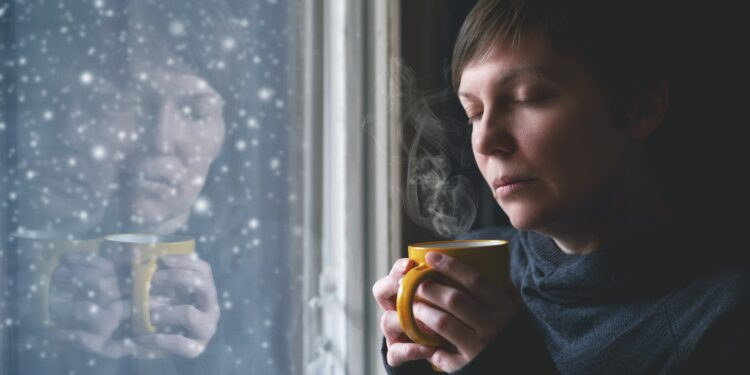 Fraurig aussehende Frau mit einer Tasse steht am Fenster
