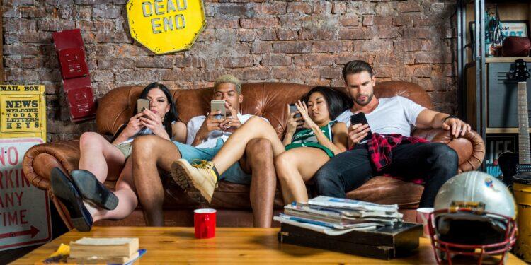 Vier Jungendliche sitzen auf einem Sofa und schauen auf ihre Smartphones.